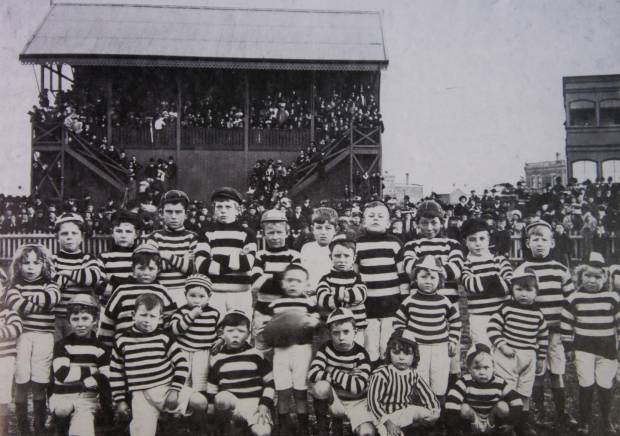 Children of brunswick players posing in front of the old grandstand at gillon oval in 1908.