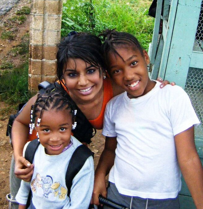 Simone Brown in Jamaica posing with two children