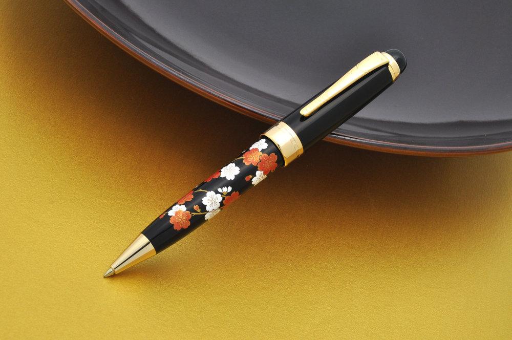 漆蒔絵 - 漆蒔絵(日本漆)塗は何層にも重ねて塗り、その後、蒔絵に最も適した金や銀の粉を振りかけます。漆黒のレジンの上に施された蒔絵は、単に印刷されたものではなく、立体的に作られています。蒔絵の美しさ、伝統的な技術が合わさることで、素晴らしい逸品がつくられるのです。
