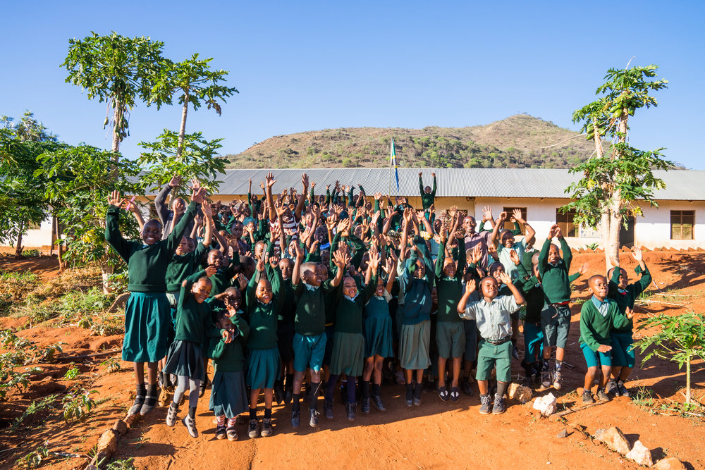 Here are the students of QEA in 2018 jumping with their teachers in front of their very own classrooms and amongst the fruit trees that they are taught to care for. Not all 203 students are pictured - you can see the nursery class with their teachers Kezia and Diana at the top of this page!