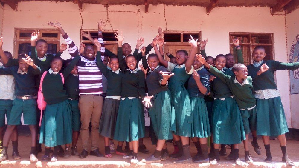 2018's Primary 7 Class celebrating their success with their brilliant head teacher and the school manager, Yohana Chuma.