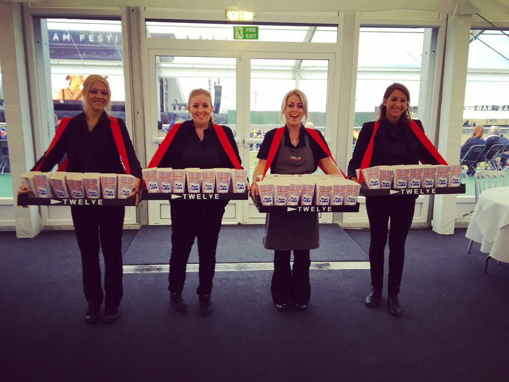 Twelve Usherettes serving up popcorn.