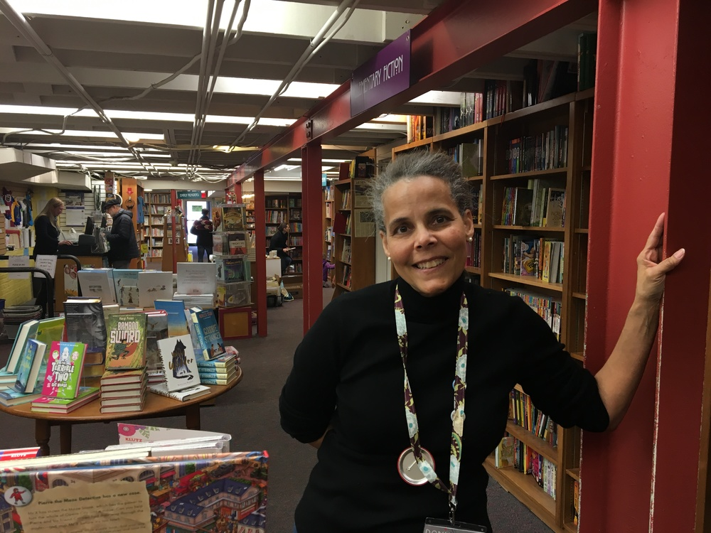Donna Wells, a children's book seller at Politics and Prose, stands in front of her section downstairs at the store. (Credit: Robin Dienel, American University)