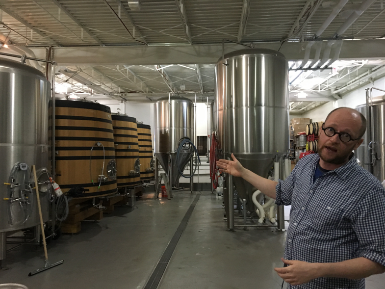 Nathan Zeender, head brewer at D.C. based Right Proper Brewing Company, standing in front their fermentation barrels. (Robin Dienel/American University)
