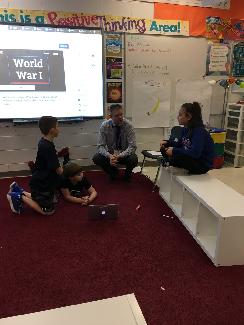 Superintendent Rosenkrance talking with students about their World War I documentaries.