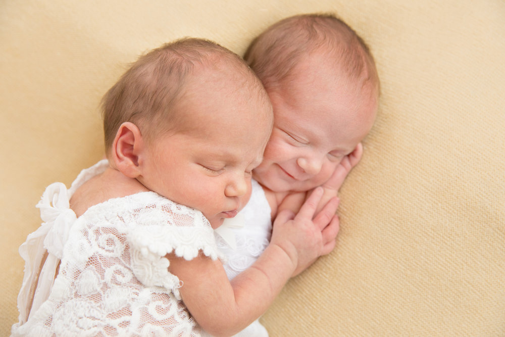 Newborn twin girls in lace outfits with one smiling as they cuddle taken at Mel Hill Photography Canberra