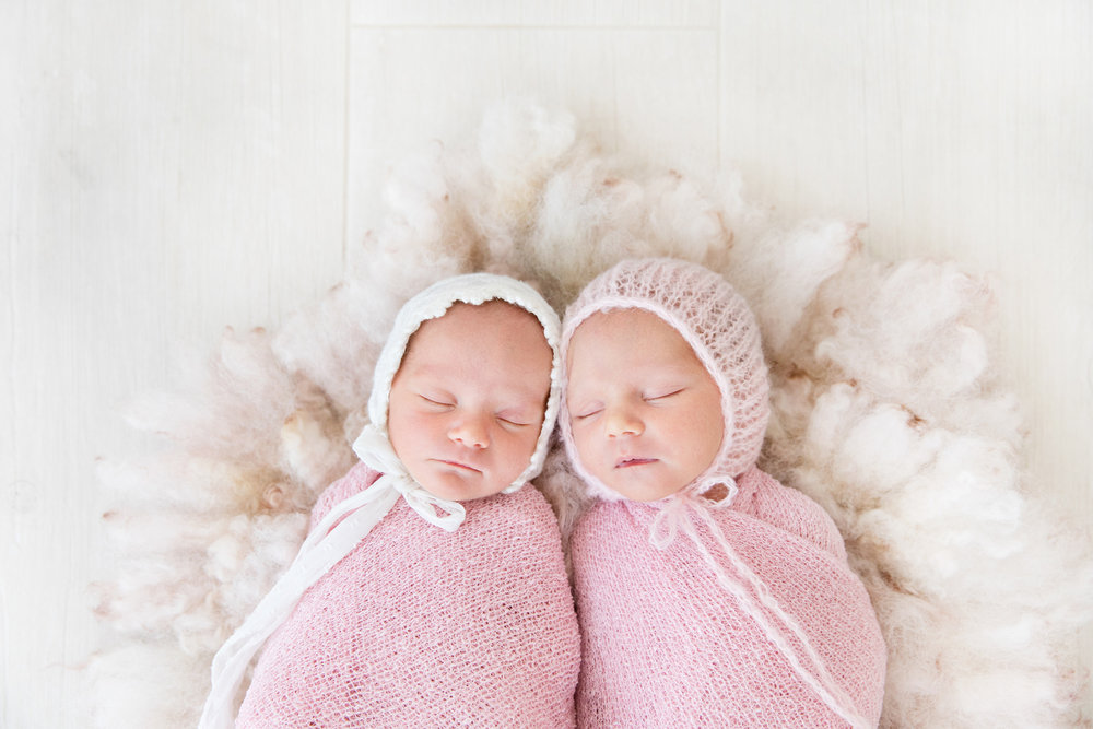 Image of newborn twin girls in pink bonnets photographed at Mel Hill Photography Canberra.