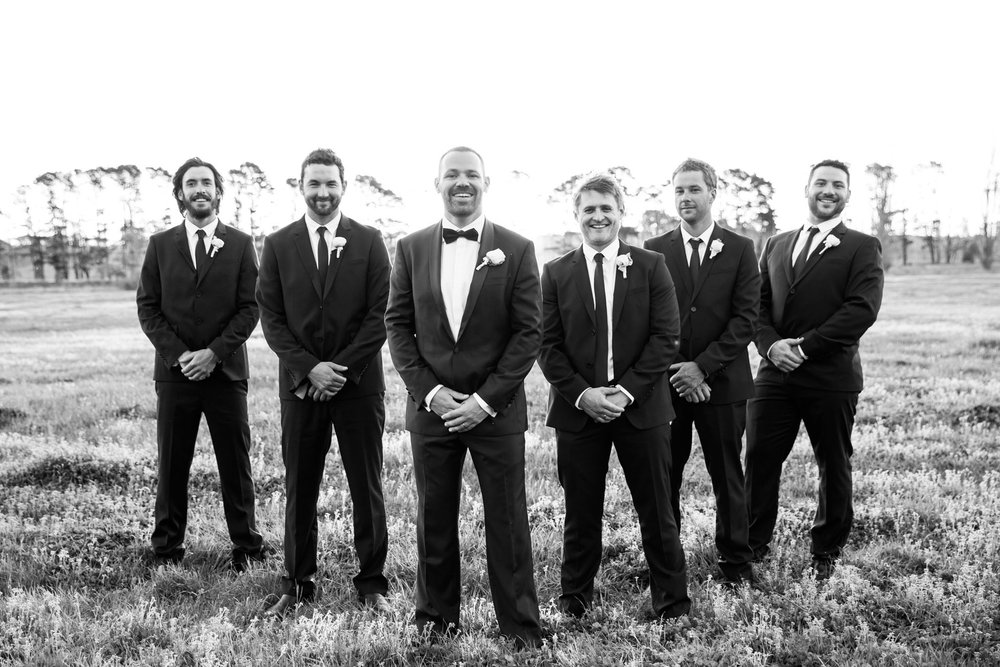 Groom and groomsmen all in suits in a country field at Grazing Gundaroo