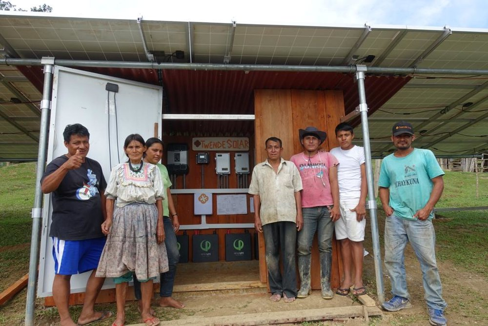 Community members stand outside the room built under the donated    Unirac    ground mount system to house the    SimpliPhi    batteries and    STUDER    power electronics. Many community members pitched in to help construct this room and lay the foundation for the array with panels donated by    Signal Energy Constructors.
