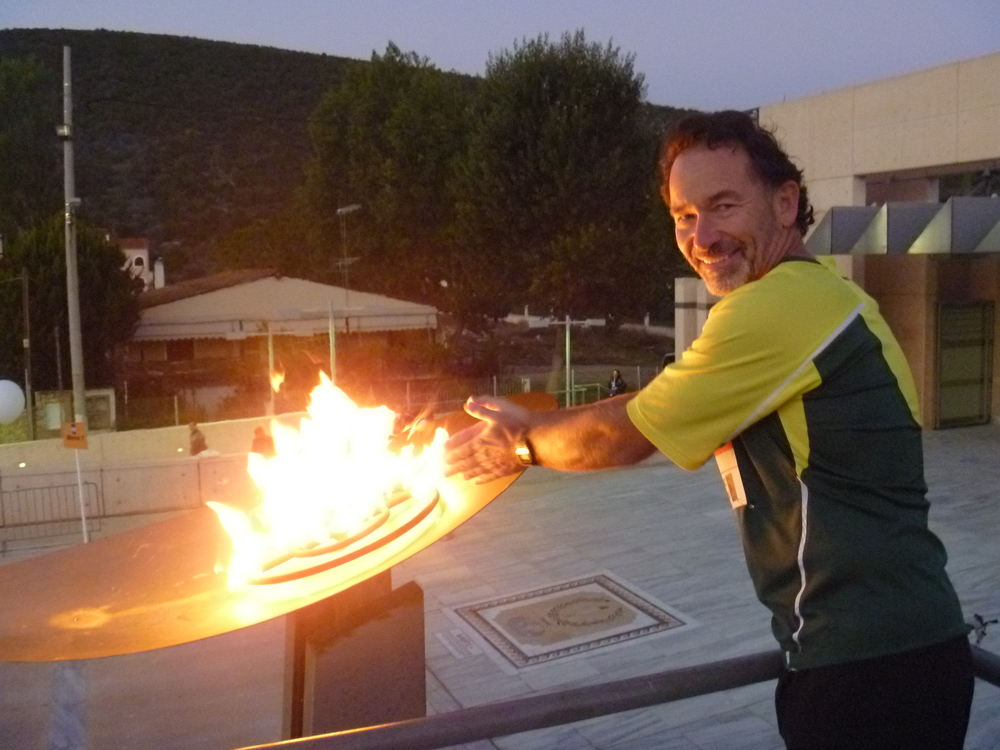 Bruce warming his hands at the Olympic flame in the town of marathon, Greece, before running the Athens marathon.