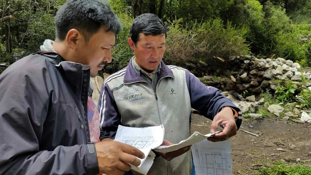 - Mingma Tenzin, Project Coordinator, and Dorme, general contractor, go over construction plans.