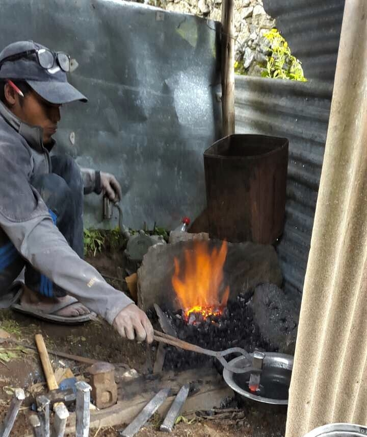 - A worker forges metal stakes over a wood fire.