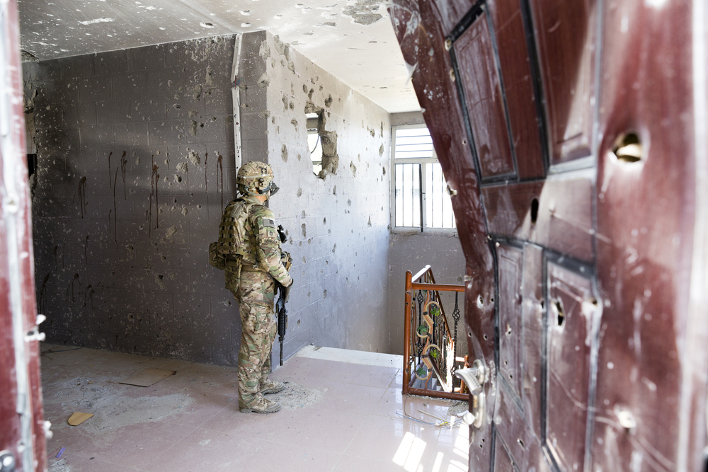 US Army Soldier standing inside the bloodied and bullet-riddled Justice Center in Farah City days after an insurgent attack (Farah, Afghanistan).