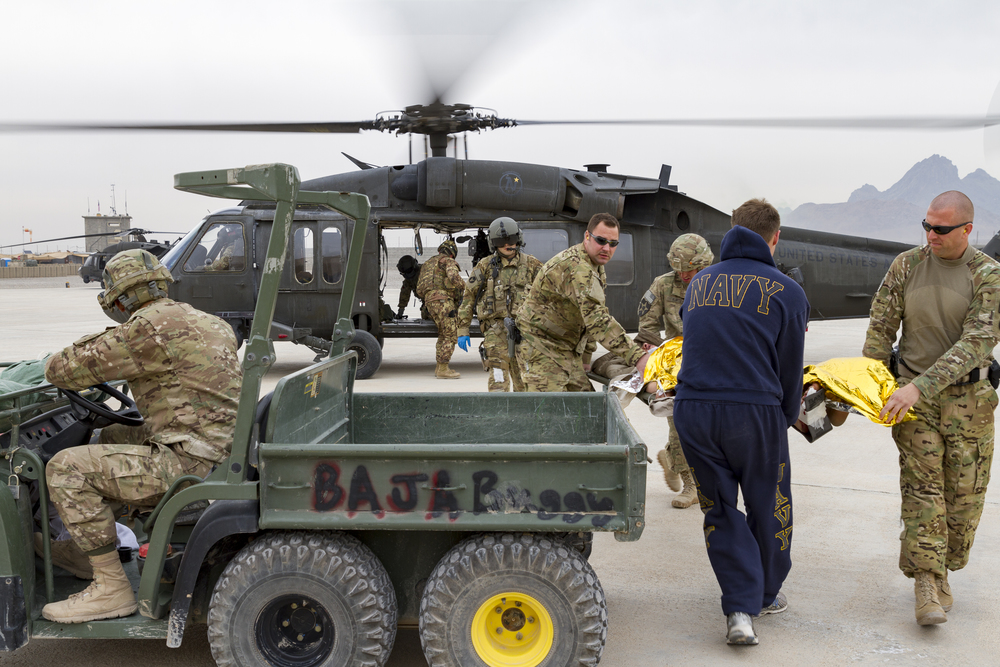 US Navy and US Army medical personnel unloading casualties from a blackhawk helicopter to an all-terrain vehicle for transport to the Base Aid Station at Forward Operating Base Farah, Afghanistan.