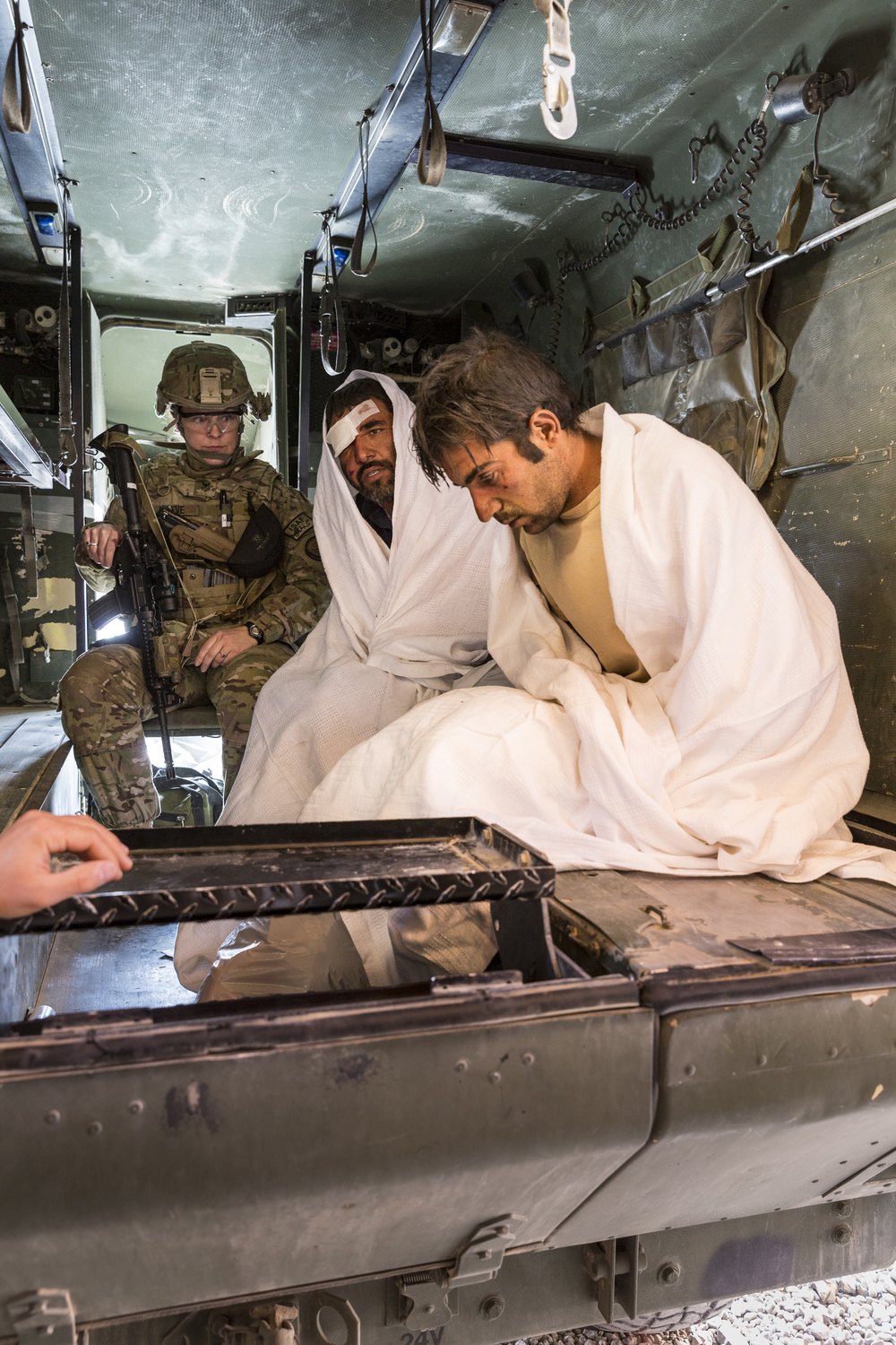 A US Navy Hospital Corpsman and two Afghan Soldiers prepare for transport in the back of a US Army ambulance at Forward Operating Base Farah, Afghanistan.