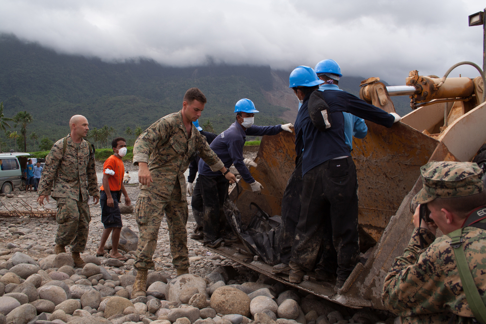 A body of a landslide victim is removed from the bucket of a front-loader at Guinsaugon, Leyte, Philippines.