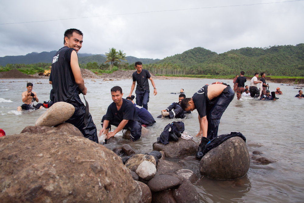 Filipino search and rescue personnel clean up in a river after a day of searching for landslide victims at Guinsaugon, Leyte, Philippines).
