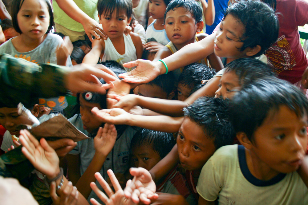 Children at the orphanage in Saint Bernard receive food from a U.S. Marine (Leyte, Philippines).