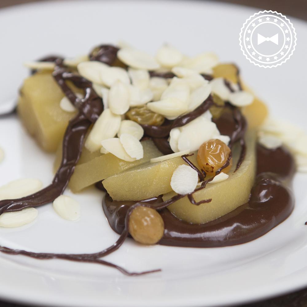 Peras escalfadas en jugo de manzana, jengibre, vainilla, azúcar morena y nuez moscada, con chocolate y pasas doradas.