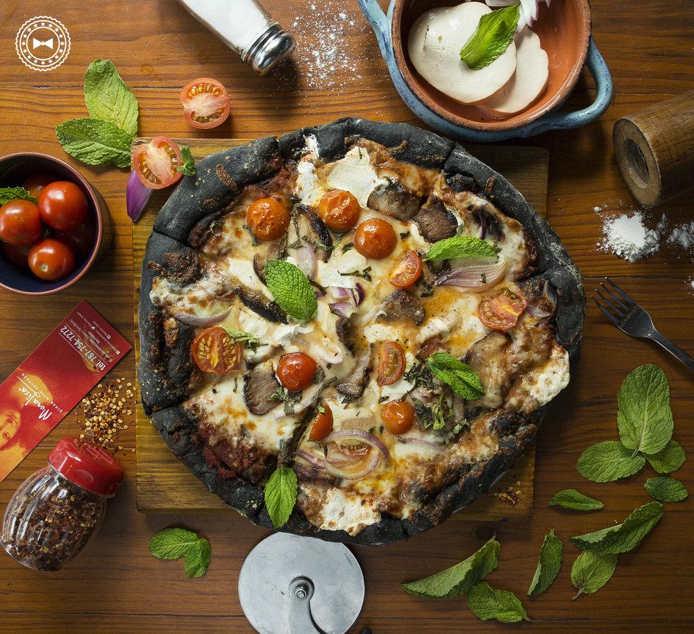 Pizza Negra (masa negra a base de tinta de calamar, salsa pomodoro, queso mozzarella ahumado, cerdo a la parrilla, cherry tomatoes, cebolla lila y hojas de menta), de Mona Lisa