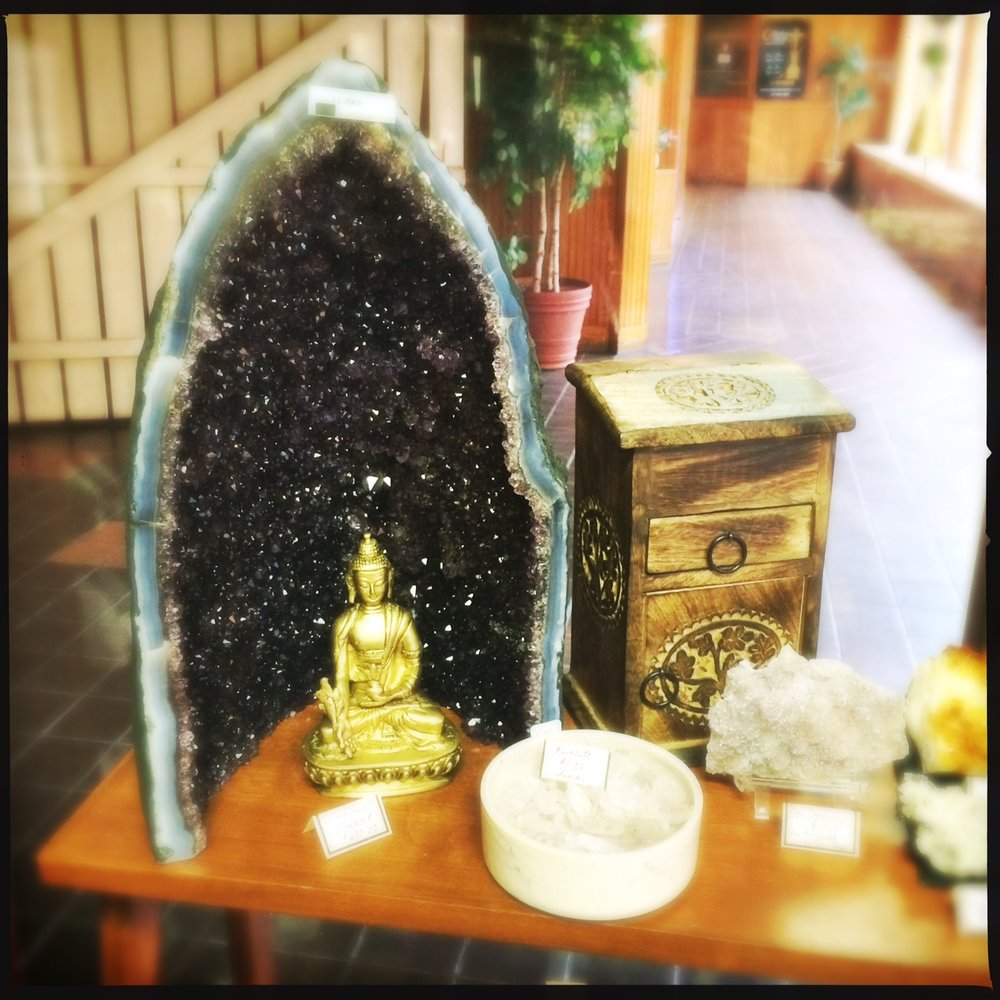 A beautiful, deep deep purple amethyst geode from Uruguay.  Hand carved wood herb cabinet from India.  Brass Buddha statue.