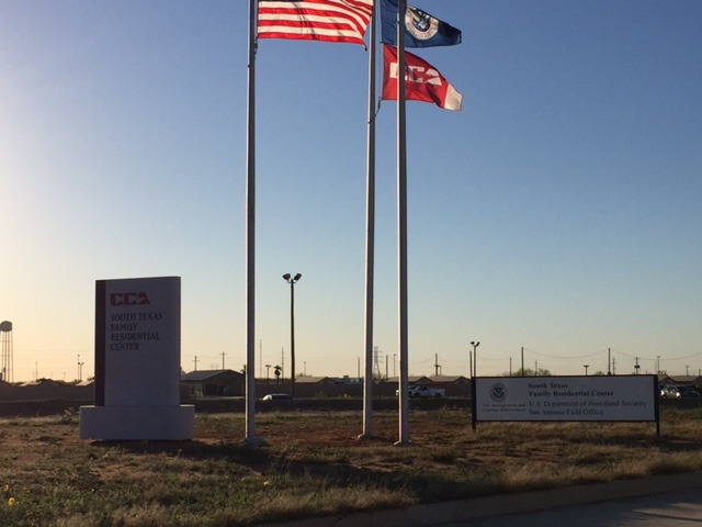 Outside the detention center in Dilley, TX—with the Corrections Corporation of America flag next to the US flag