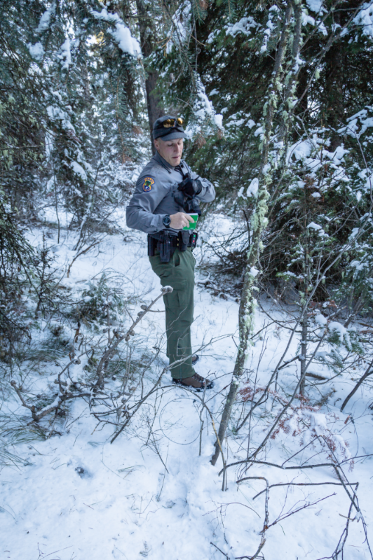 An IDFG Game Warden makes notes on a trap line set in the Targhee National Forest.