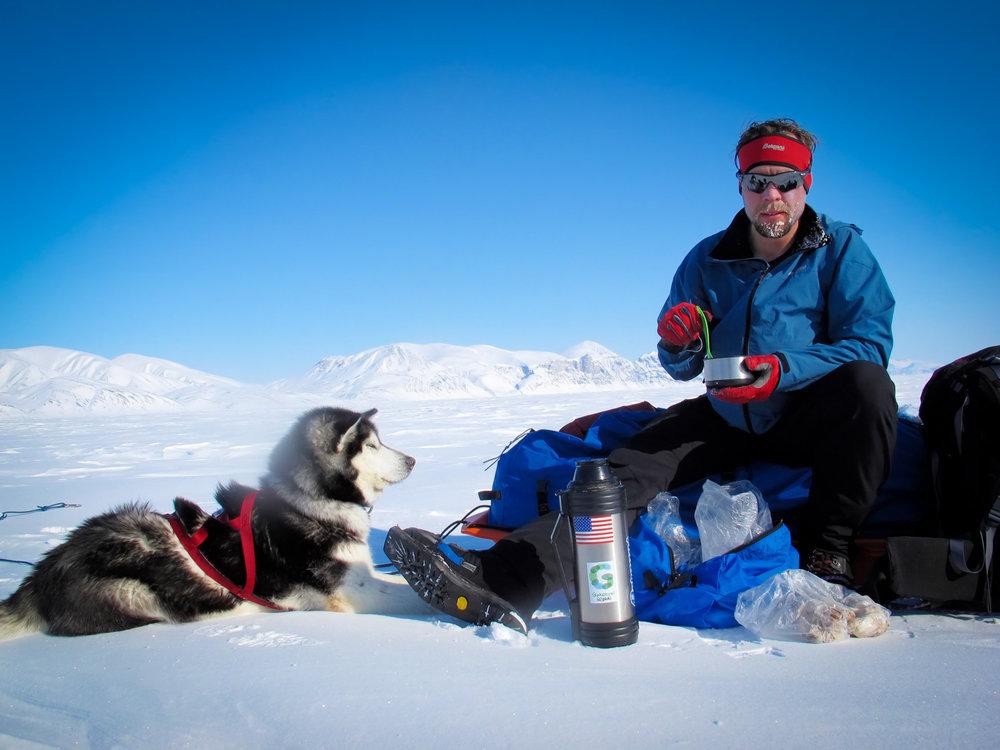 John Huston taking a sustenance break on Canada's Ellesmere Island with his skijor companion Elle. © Tobias Thorleifsson
