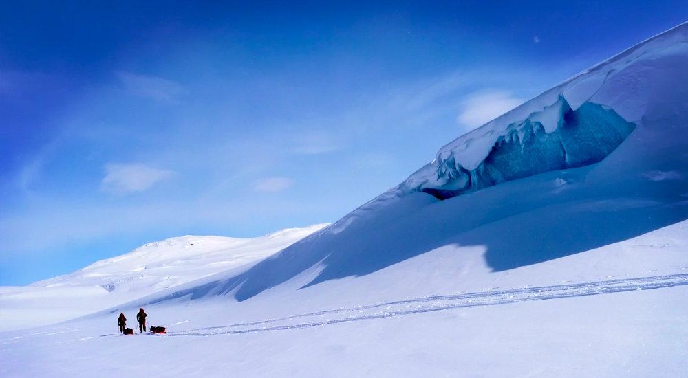 John Huston and Tobias Thorsleifsson ski past the base of the Hardangervidda glacier outside of Finse, Norway. © Kyle O'Donoghue.