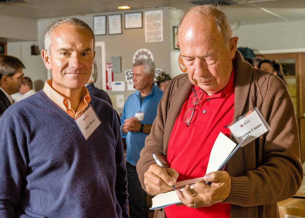 Bestselling author Stephen Coonts signs a copy of one of his books during the Clara Barton Donor Reception held by the Pikes Peak Chapter of the American Red Cross on 10/5/15.