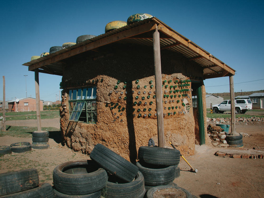 Mandel's house, built out of used tires, recycled bottles and mud with the help and instruction of Qala Phelang Tala in Springfontein, South Africa.