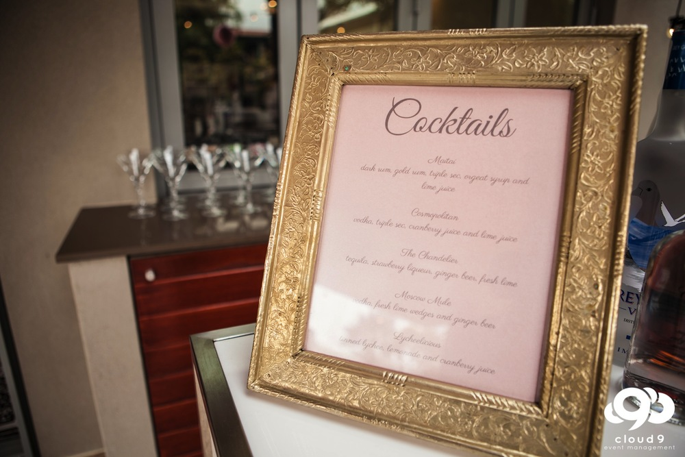 The cocktail list in gold decorated frame on the glow bar