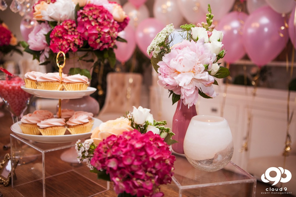 White tiered stands with gold trim, bright and soft pink flowers and tea-light candles