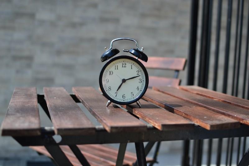 Analog alarm clock on table