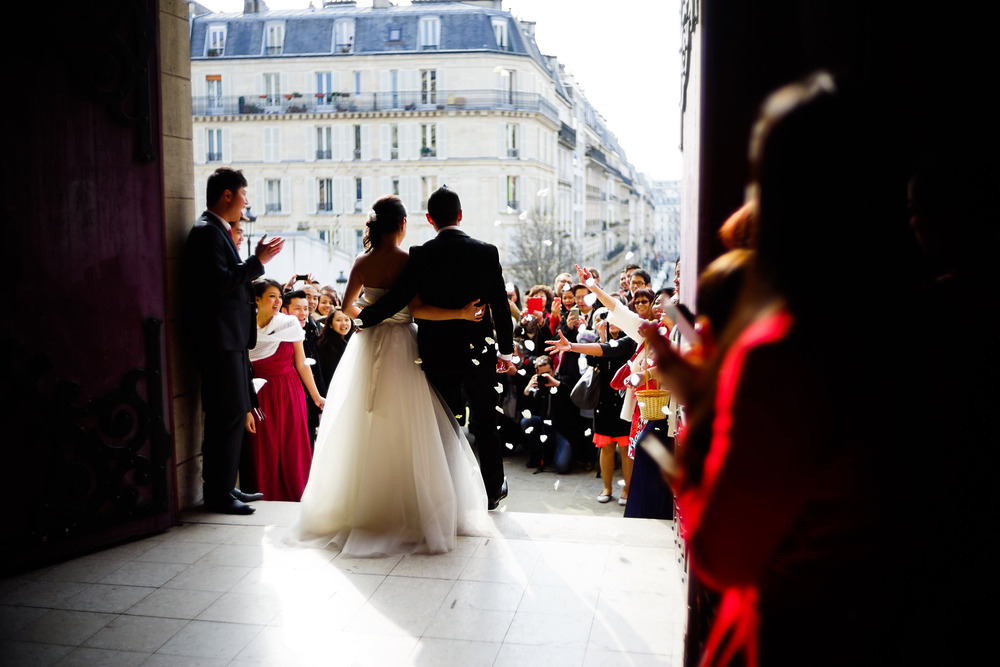 Flower petals are thrown as a young couple exit the church of their wedding.