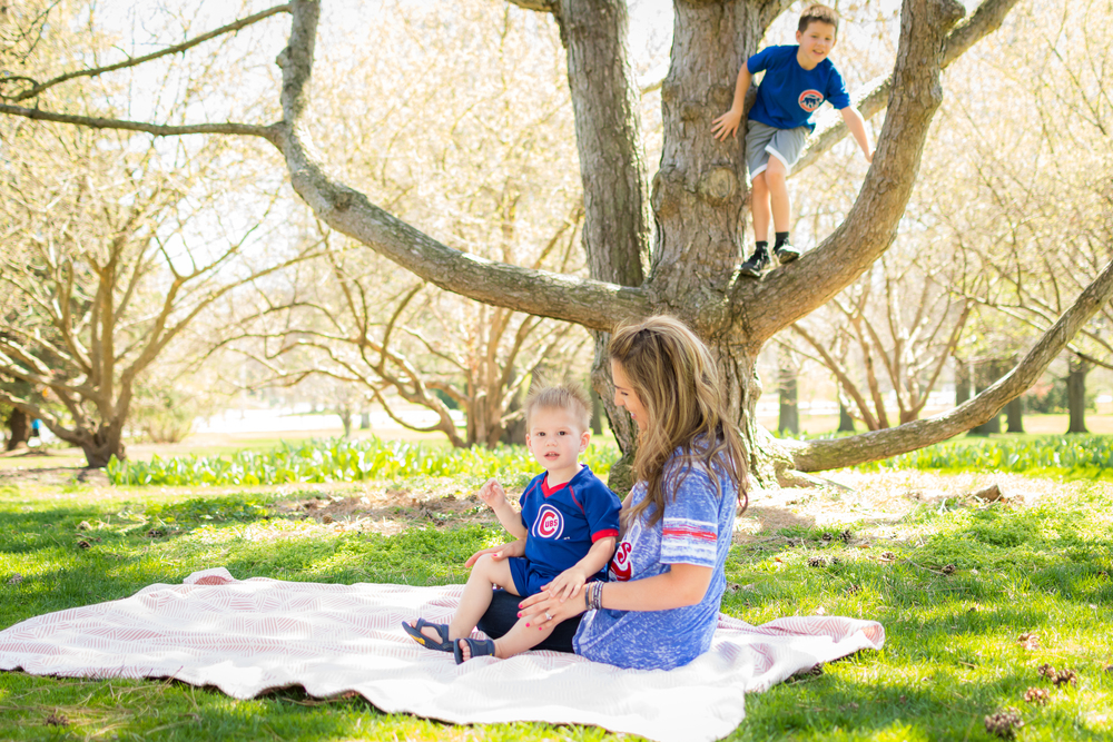 mother and toddler cuddle while brother climbs tree