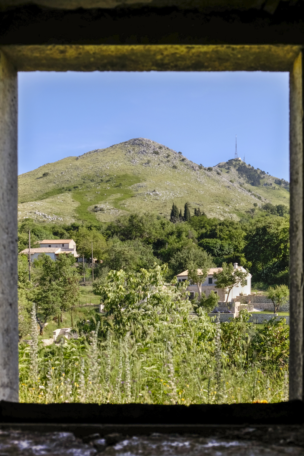 a view of the corfu moutainside through the old bakery window in palea perithia