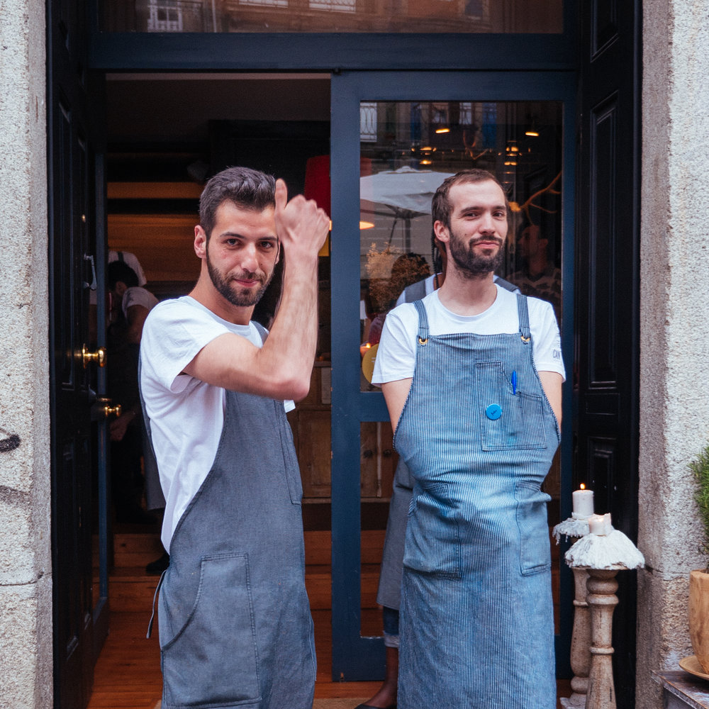 cooks standing outside their restaurant in portugal