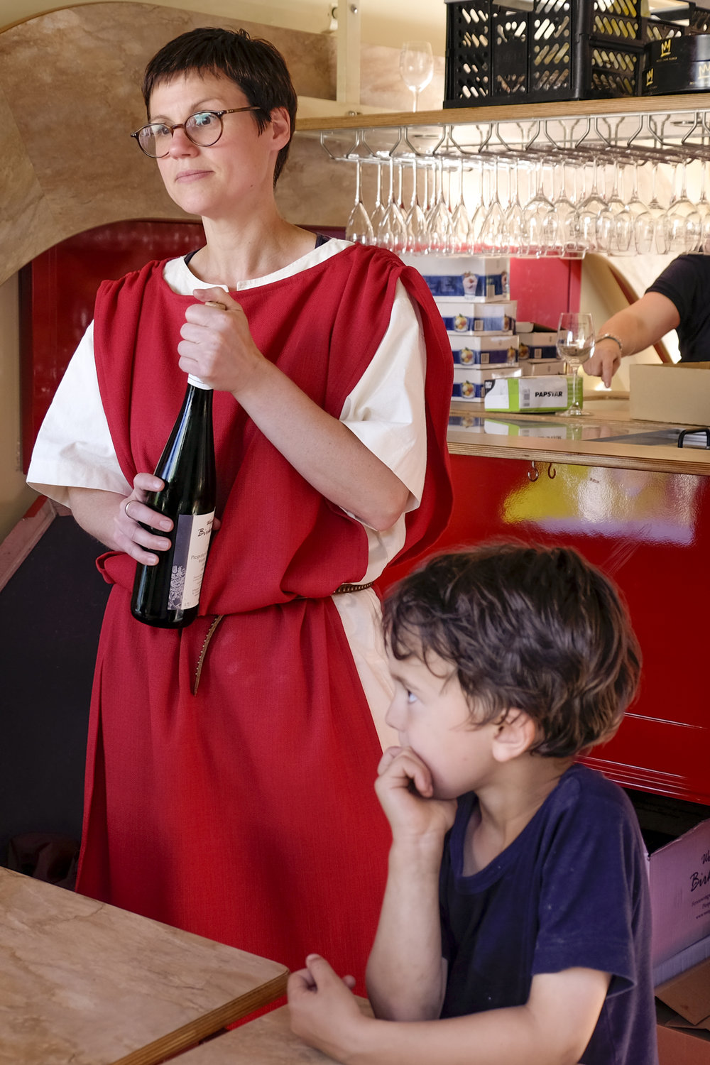 a bartender is dressed up in roman attire serving wine in piesport