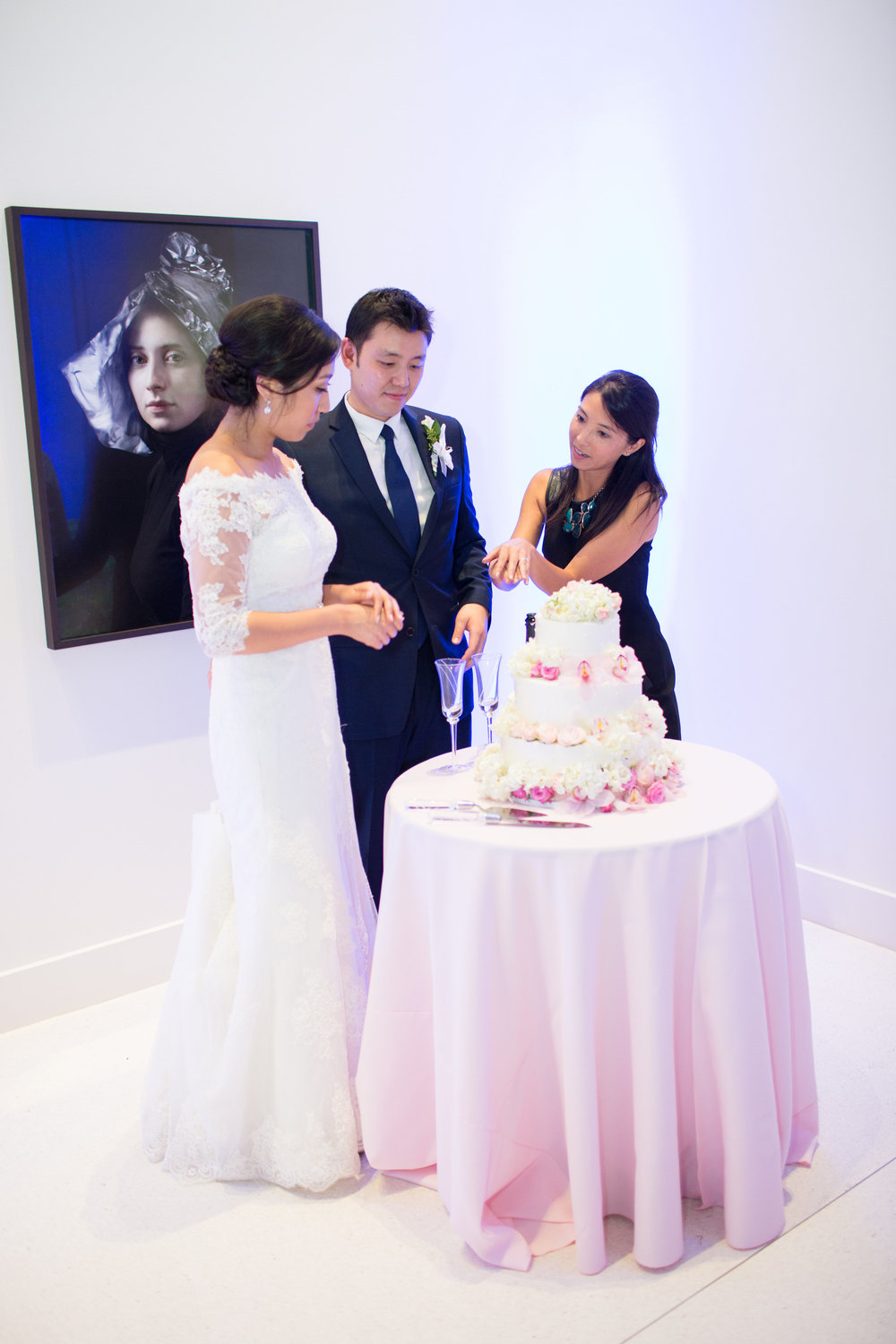 A sneak peek behind the scenes, here's Sonya teaching the Bride and Groom how to cut the cake so that the Photographer can get the best photos for the special moment. Photo by  France Photographers