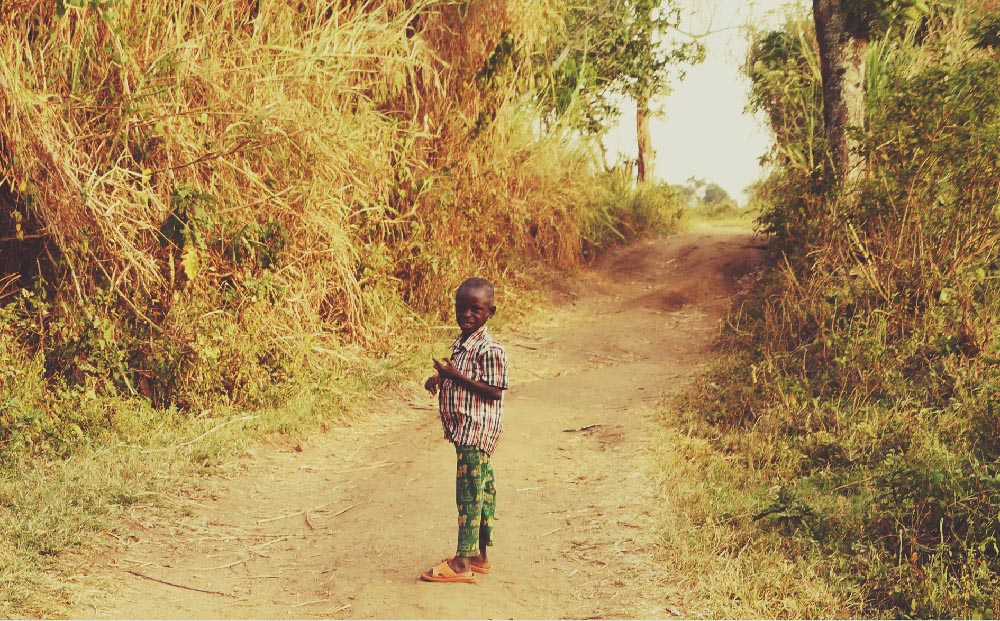 Illumelation Ugandan kid on path Kibale.jpg