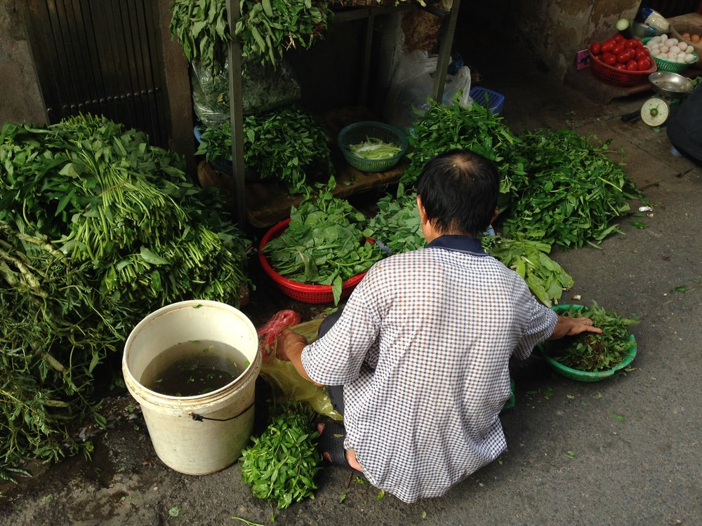 Man peeling vegetables in street, Hanoi, Vietnam - illumelation.com