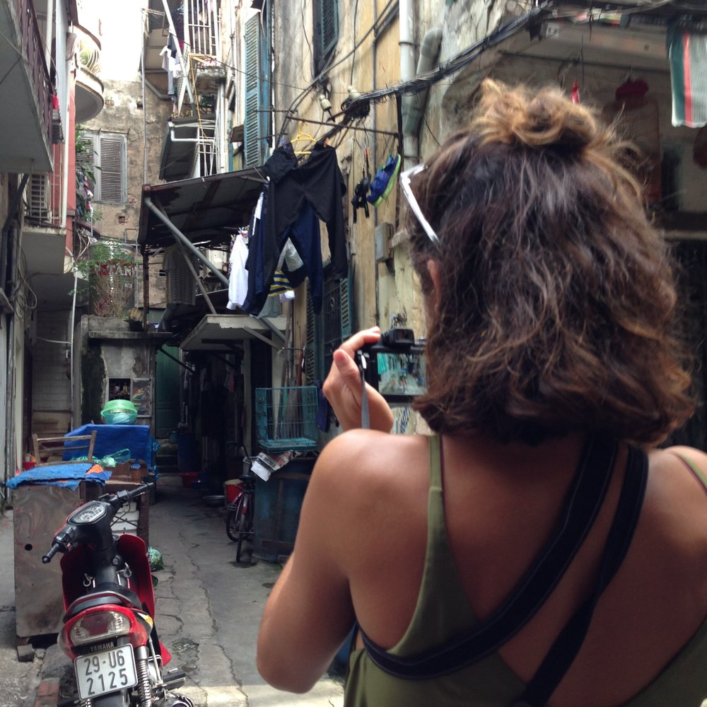 Dominique taking a picture of an alleyway in Hanoi, Vietnam - illumelation.com