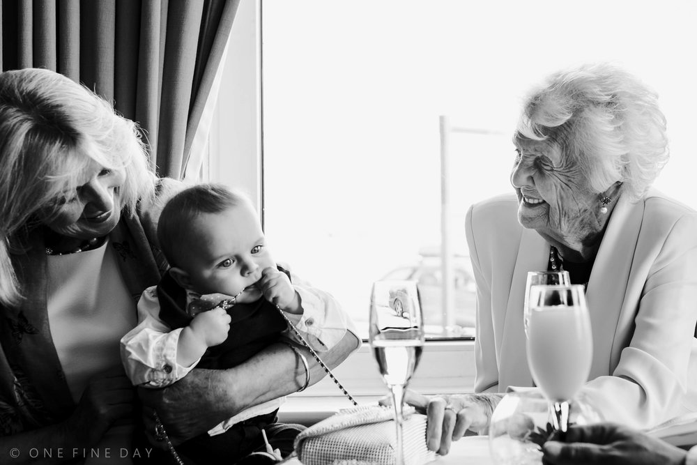 A moment between three generations of the same family photographed at a wedding in Northern Ireland