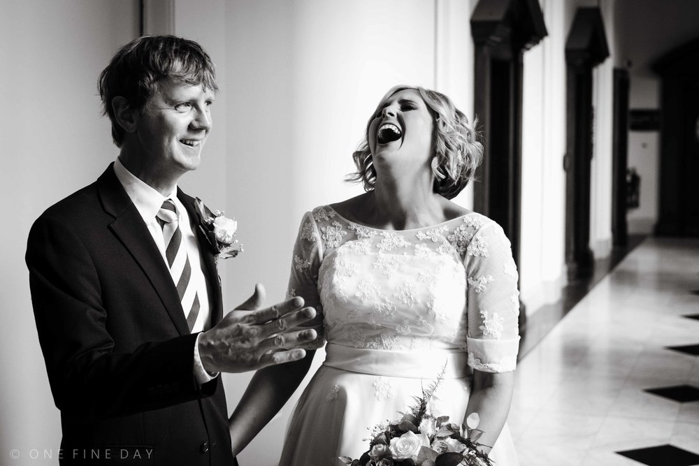 Natural and un-posed documentary style picture of the bride and groom laughing at a belfast city hall wedding in black and white