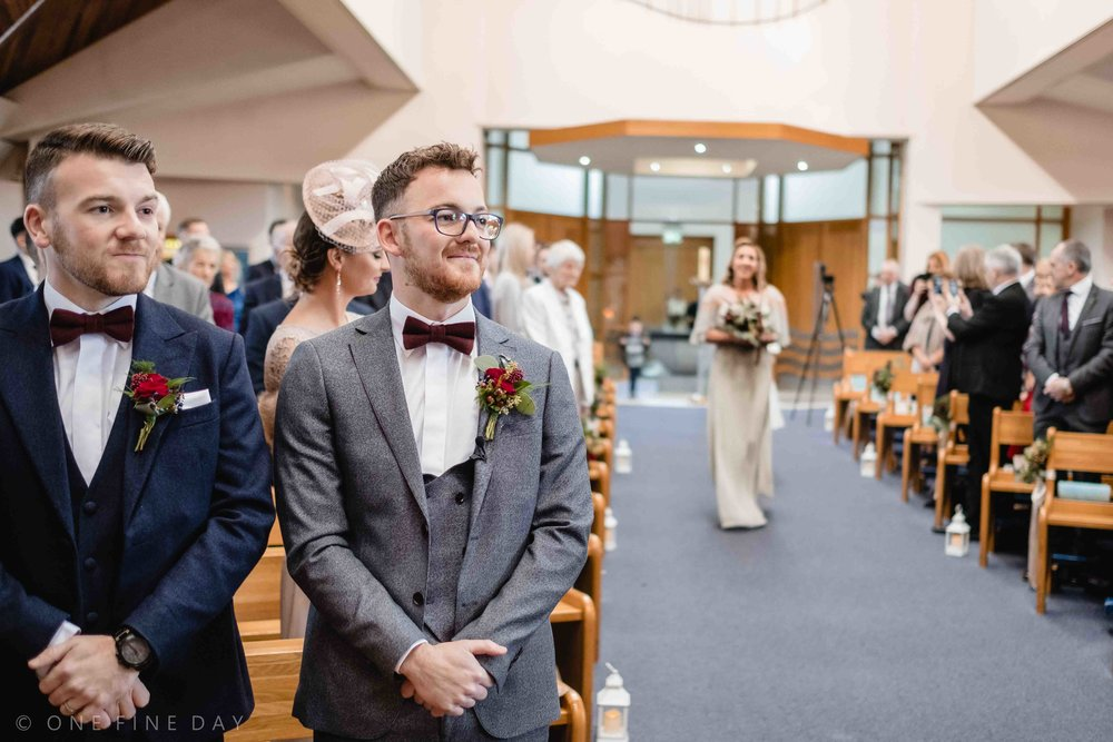 Groom at top of the aisle in natural wedding photograph
