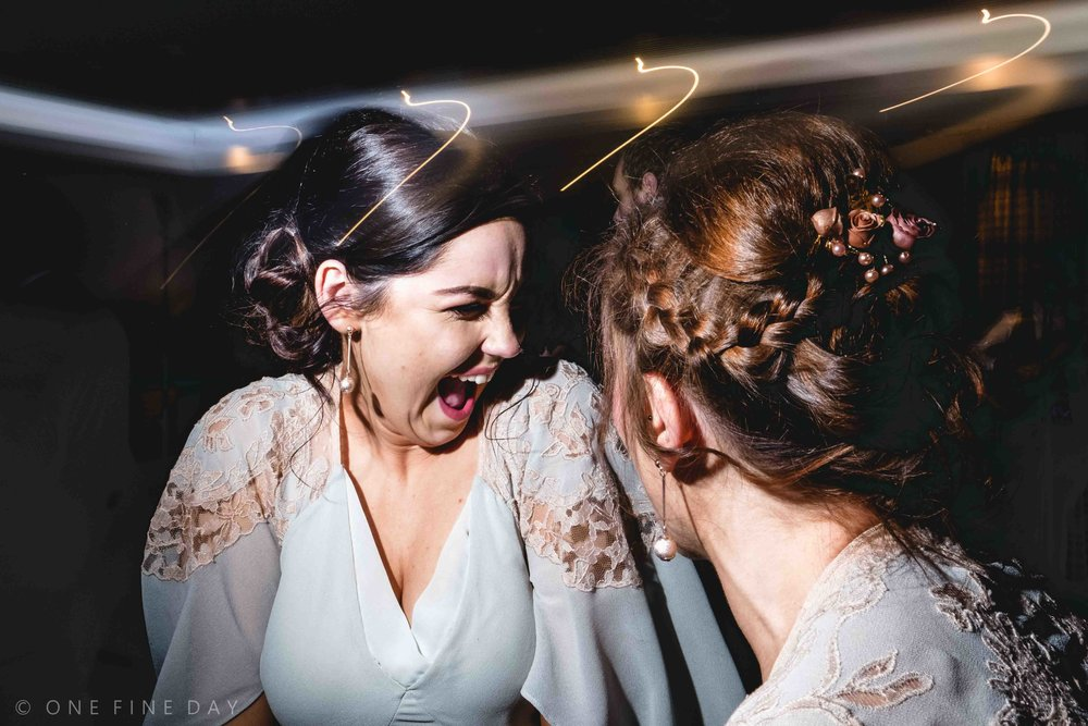 Bridesmaids laughing in natural wedding photograph