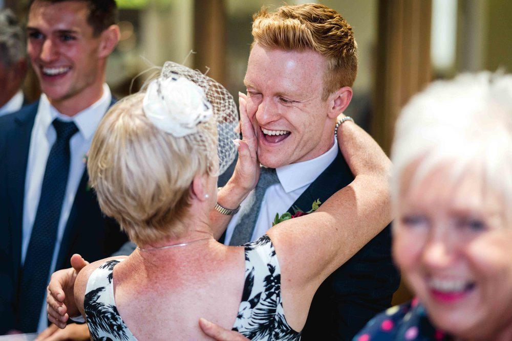 Natural un-posed photo of Laughing Groom at his wedding