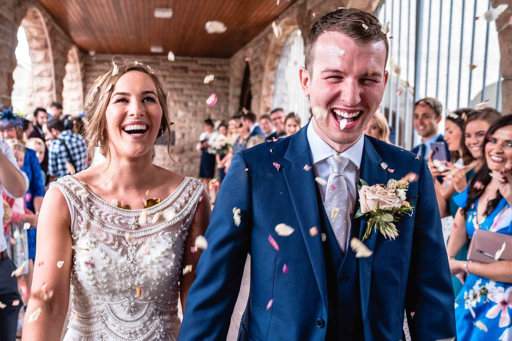 Natural photograph of Bride and Groom in the middle of wedding confetti