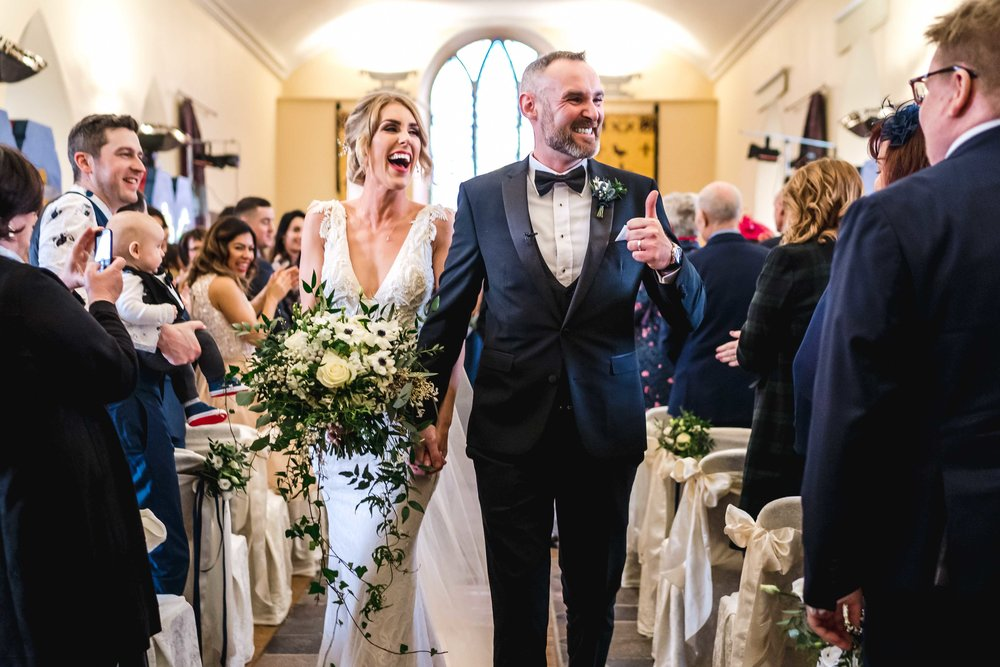 Bride and Groom happy as they walk down the aisle after getting married in Carlingford Heritage Centre, Ireland